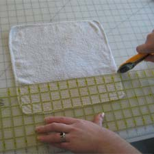 Cutting old washcloth into baby wipes