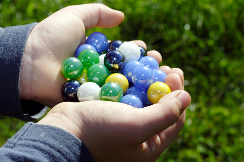 Child with Hands Full of Marbles