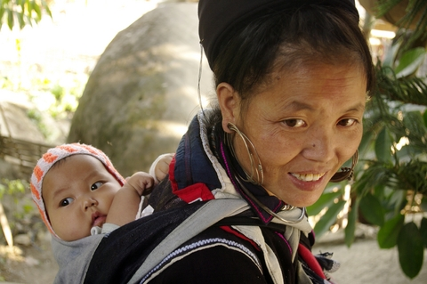 A Black Hmong woman carries her baby on her back