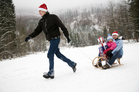 Family sledding with holiday gifts