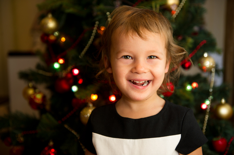 Child in front of a Christmas tree