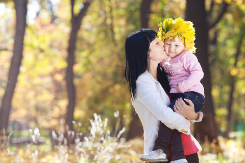 Mother holds a child wearing an autumn leaf crown
