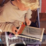 Child weaving on a wooden loom
