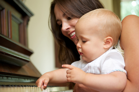 Mother teaching baby to play piano