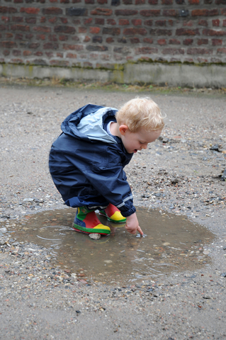 Toddler play in a rain puddle