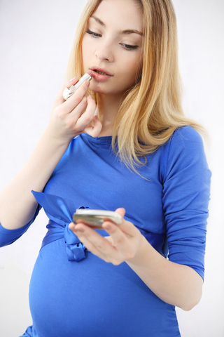 Pregnant woman putting on lipstick
