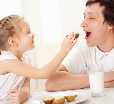 Young girl feeding her father breakfast