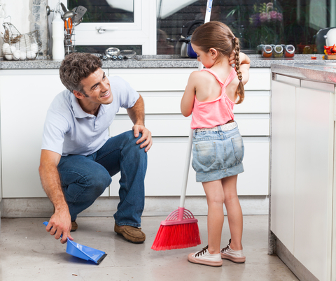 Father and toddler sweeping kitchen