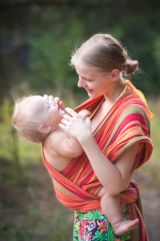 Mother wearing baby in a long fabric wrap baby carrier