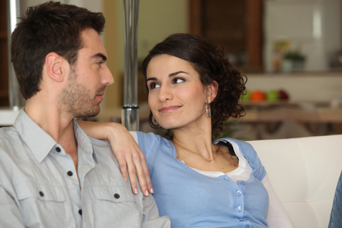 Young married couple sitting together on couch