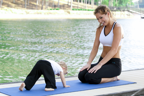 Mother teaching baby yoga