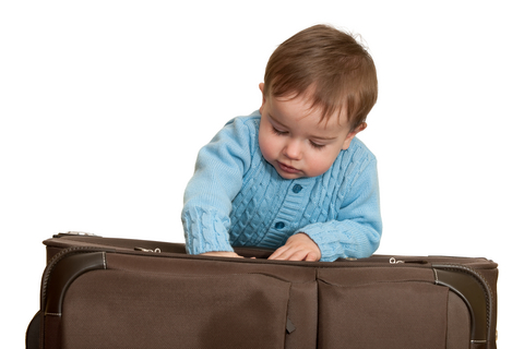 Baby packing a suitcase