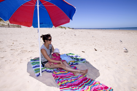 Mother and baby in the shade at the beach