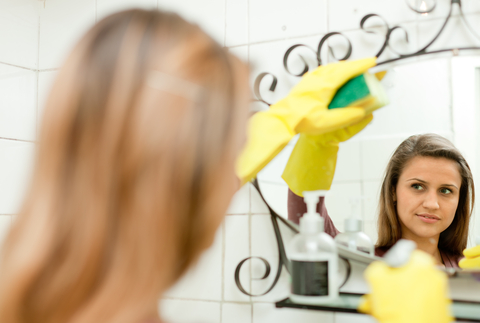 Woman cleaning a mirror