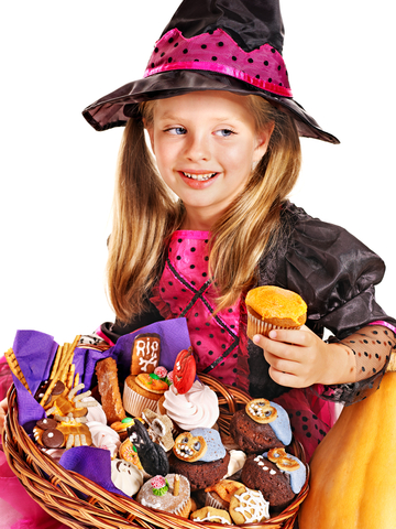 Child dressed in Halloween costume eating cupcake