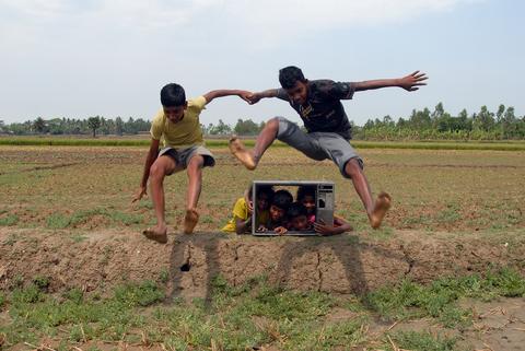 Children playing around a television