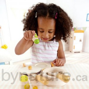 Child with toy cooking set