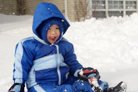 Toddler sitting in the snow licking his face